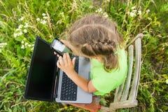 Ragazza del bambino con il computer portatile ed il telefono in natura immagini stock libere da diritti