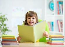 Ragazza del bambino con il libro aperto a casa Immagine Stock