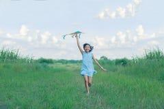 Ragazza del bambino con un funzionamento dell'aquilone e felice asiatici sul prato nel riassunto immagine stock libera da diritti