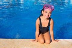 Ragazza del bambino degli occhi azzurri sulle ginocchia sul poolside blu del raggruppamento fotografia stock
