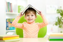 Ragazza del bambino del bambino in età prescolare con il libro sopra la sua testa Fotografie Stock