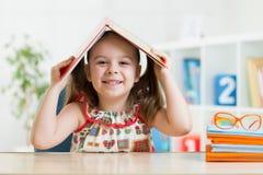 Ragazza del bambino del bambino in età prescolare con il libro sopra la sua testa Fotografia Stock