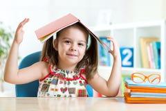 Ragazza del bambino del bambino in età prescolare con il libro sopra la sua testa Fotografie Stock Libere da Diritti