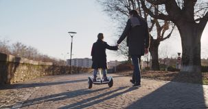 Ragazza del bambino della figlia che impara guida segway con l'insegnamento del papà nella città Tecnologia futura moderna di tra video d archivio