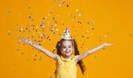 Ragazza del bambino di buon compleanno con i coriandoli su fondo giallo immagini stock libere da diritti