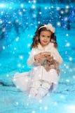 Ragazza del bambino di Natale sul fondo dell'albero di inverno, neve, fiocchi di neve Immagine Stock