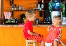 Ragazza del bambino e del ragazzino che si siede alla barra Fotografia Stock