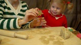 Ragazza del bambino e della donna che prepara pan di zenzero per la cena di notte di Natale della famiglia video d archivio