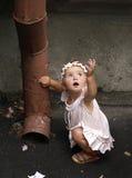 Ragazza del bambino e tubo dell'acqua piovana Immagini Stock