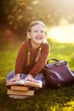 Ragazza del bambino in età prescolare pronta di nuovo alla scuola, leggente i manuali Immagini Stock Libere da Diritti