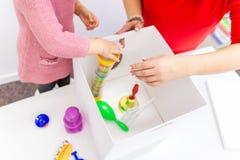 Ragazza del bambino nella sessione di terapia occupazionale del bambino che fa gli esercizi allegri sensoriali con il suo terapis immagini stock libere da diritti