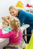 Ragazza del bambino nella sessione di terapia occupazionale del bambino che fa gli esercizi allegri sensoriali con il suo terapis fotografie stock