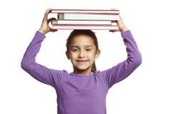 Ragazza del banco con i libri sulla sua testa Immagine Stock