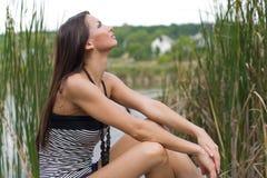 Ragazza del Brunette che si siede e che osserva in su fotografie stock