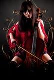 Ragazza del Brunette nel colore rosso con il violoncello Fotografie Stock