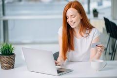 Ragazza del cliente che compra online con un computer portatile e una carta di credito Immagini Stock