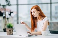 Ragazza del cliente che compra online con un computer portatile e una carta di credito Fotografia Stock