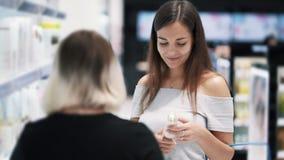Ragazza del compratore che parla con commesso in deposito cosmetico, movimento lento