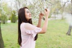 Ragazza del fondo della primavera che gode dell'odore in un giardino di fioritura Copi lo spazio Giovane donna felice immagine stock libera da diritti