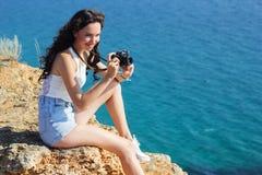 Ragazza del fotografo che fa le immagini dalla vecchia macchina fotografica sulla cima della montagna Fotografie Stock