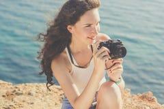 Ragazza del fotografo che fa le immagini dalla vecchia macchina fotografica sulla cima della montagna fotografia stock libera da diritti