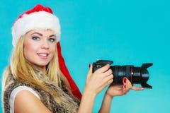 Ragazza del fotografo nelle immagini della fucilazione del cappello del Babbo Natale Fotografia Stock