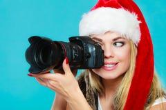 Ragazza del fotografo nelle immagini della fucilazione del cappello del Babbo Natale Immagine Stock