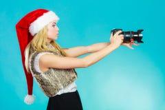 Ragazza del fotografo nelle immagini della fucilazione del cappello del Babbo Natale Immagini Stock