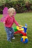 Ragazza del litlle della farfalla che gioca con un triciclo Immagini Stock