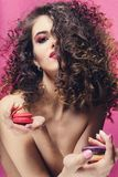 Ragazza del modello di moda di bellezza con il manicure colourful che prende i maccheroni variopinti fotografia stock libera da diritti