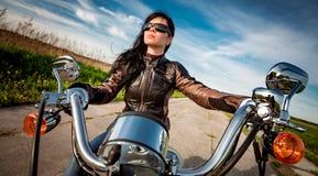 Ragazza del motociclista che si siede sul motociclo Immagini Stock