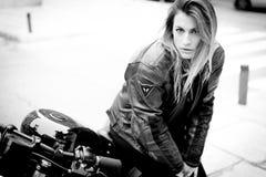 Ragazza del motociclista in un bomber su un motociclo immagini stock libere da diritti