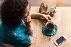 Ragazza del mulatto di Dreamful che gode del caffè in caffè Immagine Stock