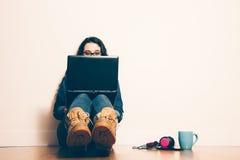Ragazza del nerd che si siede sul pavimento con un computer portatile Immagini Stock Libere da Diritti