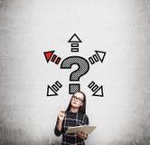 Ragazza del nerd in vestito e punto interrogativo con le frecce Fotografie Stock Libere da Diritti