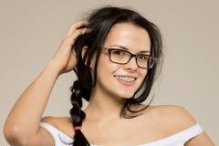 Ragazza del nerd in vetri e sostegni sui denti Pantaloni a vita bassa positivi e eccellenti della donna dello studente immagine stock