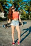 Ragazza del pattinatore che posa con un pattino vicino alle palme sulla spiaggia Donna in clothers colourful Fotografie Stock