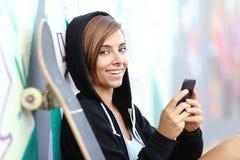Ragazza del pattinatore dell'adolescente che per mezzo di uno Smart Phone che esamina macchina fotografica Immagine Stock