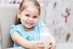 Ragazza del piccolo bambino che beve un latte fotografia stock