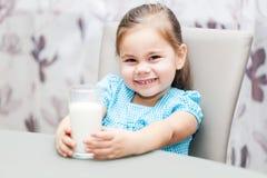 Ragazza del piccolo bambino che beve un latte immagine stock