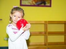 Ragazza del piccolo bambino che gioca con la palla nell'asilo nella classe della scuola materna di Montessori Bambino adorabile n Immagini Stock