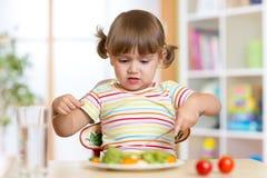 Ragazza del piccolo bambino che rifiuta di mangiare la sua cena fotografia stock