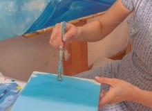 Ragazza del pittore con la spazzola, pitture una piccola tela Fotografie Stock Libere da Diritti