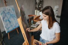 Ragazza del pittore dell'artista giovane bella Lavoro creando processo Pittura sul cavalletto Lavoro ispirato immagini stock