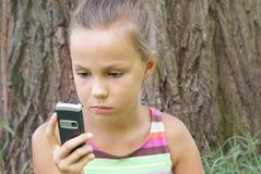Ragazza del Preteen con il telefono delle cellule Fotografie Stock Libere da Diritti