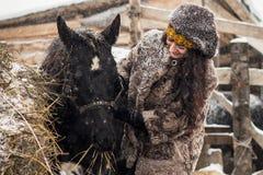 Ragazza del primo piano che segna giovane puledro sveglio nella neve fotografie stock
