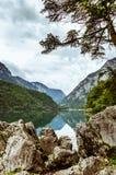 Ragazza del punto turistico dell'Austria Leopoldsteinersee su una roccia sopra il lago Fotografia Stock