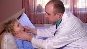 Ragazza del ragazzino che ha la gola e testa del controllo di medico del pediatra del controllo sanitario archivi video