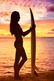 Ragazza del surfista che pratica il surfing esaminando tramonto della spiaggia dell'oceano Fotografie Stock