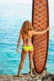 Ragazza del surfista nel supporto del surf della tenuta del bikini sull'alta scogliera Fotografie Stock Libere da Diritti
